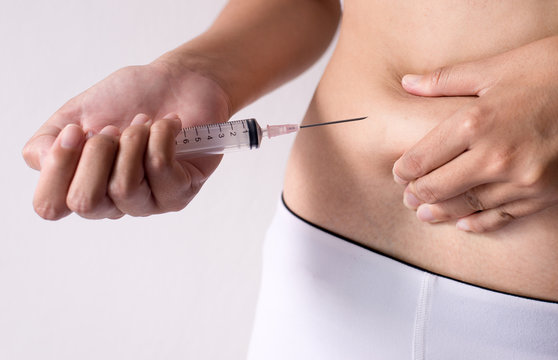 Asian woman using syringe inject medicine to her belly,Cellulite mesotherapy,Excess fat