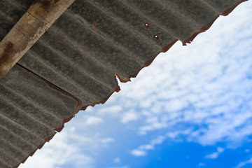old rusty zinc roof with cloudy blue sky background