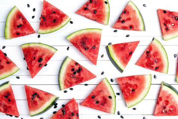 Sliced watermelon on white wooden background.