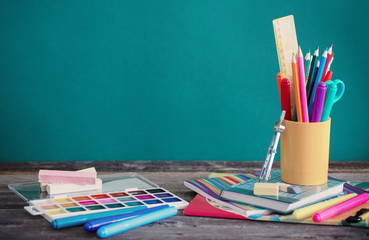 school supplies on wooden table on green background