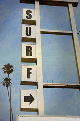 aged and worn vintage surf sign with palm trees