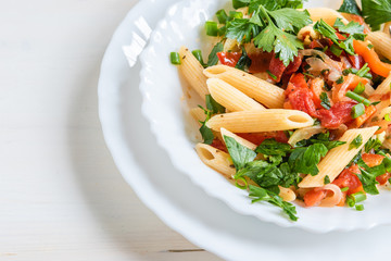 Traditional Italian pasta with peppers and tomatoes and parsley in a bowl close-up, penne