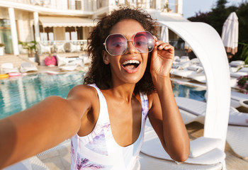 Attractive young african woman in swimsuit taking a selfie