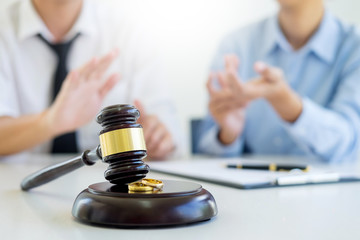 Angry couple arguing telling their problems to Judge gavel deciding on marriage to conclude an agreement on the divorce. They quarrel and argue with each other