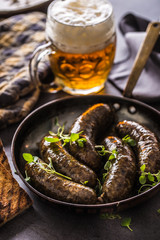 Roasted sausages in pan with bread herbs and draft beer.