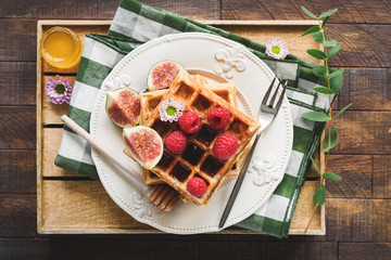 Belgian waffles with figs, raspberries and honey on wooden serving tray. Top view of tasty breakfast