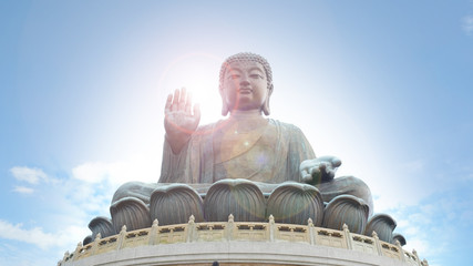 Tian Tan Buddha with sun flare in the hand and blue sky background located at Ngong Ping, Lantau Island, in Hong Kong