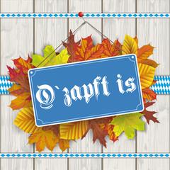 Blaues Schild O zapft Is hängend an einer Holzwand mit Herbstlaub