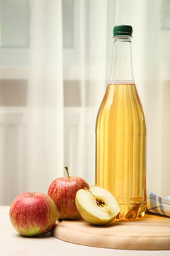 Apple cider in a bottle on the window background.