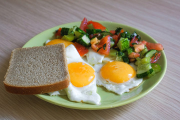 delicious fried chicken eggs with salad and bread on a plate