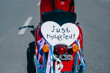 """retro scooter with ribbons and """"just married"""" heart symbol for wedding"""