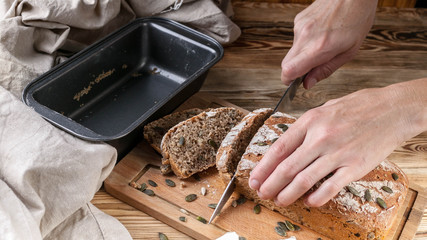 Female hands cut homemade rye bread on a wooden table
