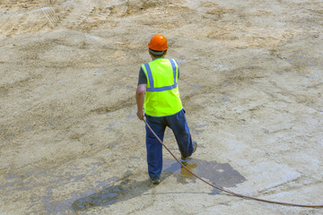 Worker at the construction site water from a hose
