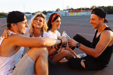 a group of young people with glass bottles with a drink standing near the supermarket, sitting on the asphalt, friends come off in full, cheerful mood, Sunny day, Lifestyl concept