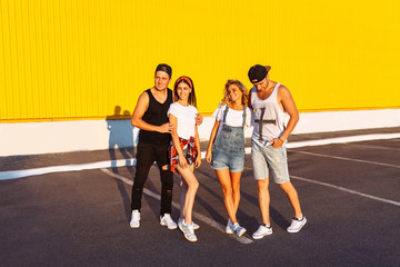 Beautiful cool young people posing on a yellow background, a group of young people resting and having fun, summer mood, friends walking in the city in a place, lifestyle