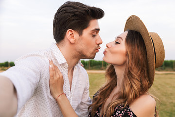 Romantic beautiful couple man and woman taking selfie together ,while kissing outdoor during summer holiday
