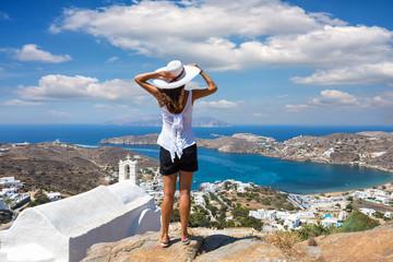 Touristin mit weißem Hut genießt die Aussicht auf die Stadt und die Landschaft der Insel Ios auf den Kykladen in Griechenland