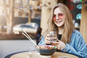 Good-looking happy young urban female student in denim jacket over black t-shirt, holding glass of water and gazing with broad smile aside, eating in asian restaurant with chopsticks