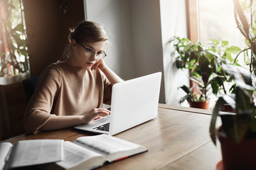 Cute european female coworker in glasses sitting near window in cafe, leaning head on hand and reading articles in network via laptop, searching information for work, making notes in notebook