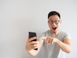 Wow face of man shocked what he see in the smartphone.