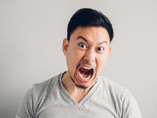 Headshot photo of Asian man with angry and furious face. on grey background.