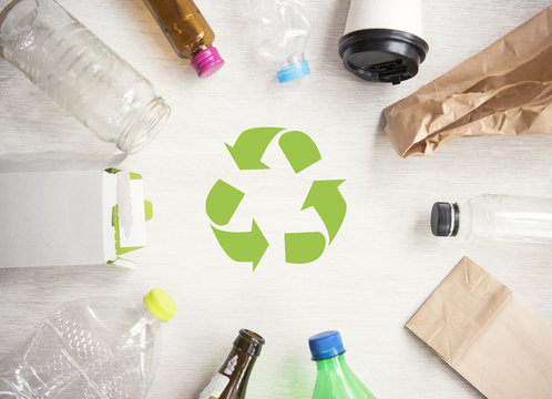 recycle symbol and plastic, paper, glass on wood table background top view. eco and save the earth concept.