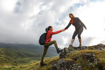 Girls helping each other hike up a mountain at sunrise. Giving a helping hand, and active fit lifestyle concept.