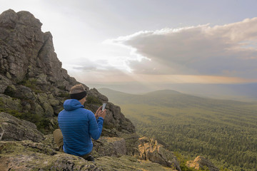 Man hiker on a top of a mountain in the national park of nature Taganay taking a photo, Russia