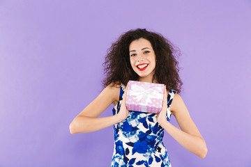 Portrait of a beautiful young woman holding present box