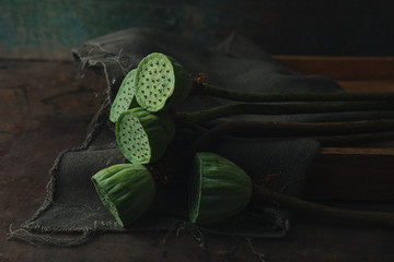 Lotus seed pods on wooden tray. Dark background