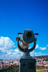 Abstract observation telescope, panoramic view of the abstract european city with red roofs, summer time.