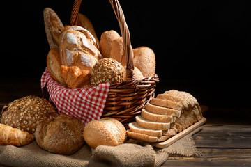 Bread and rolls in wicker basket on burlap sack
