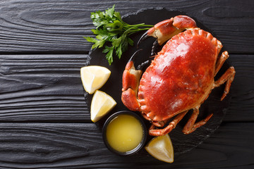 Delicious traditional boiled whole brown crab with sauce, lemon and parsley on a slate board close-up. Horizontal top view