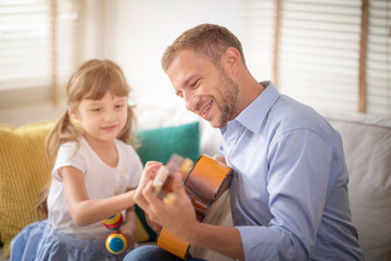 Happy dad and daughter are playing instruments together at home. Dad teach daughter play guitar. Setup studio shooting. Selective focus at father's face.