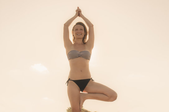 A woman sunbathing on the beach standing on rocks in a yoga pose having folded her palms above her head while standing on one leg