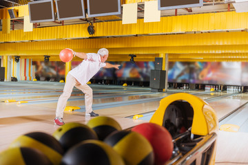 Favourite game. Pleasant nice man playing bowling while resting during the weekend