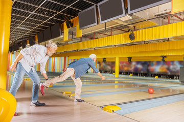 Entertainment for men. Nice positive men having fun while playing bowling together