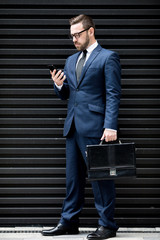Young successful handsome male in business dress and eyeglasses with briefcase and mobile phone standing near black profiled sheeting