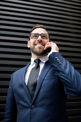 Young successful handsome smiling male in business dress, eyeglasses talking mobile phone standing near black profiled sheeting and looking away