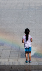 Kid in the fountain with rainbow