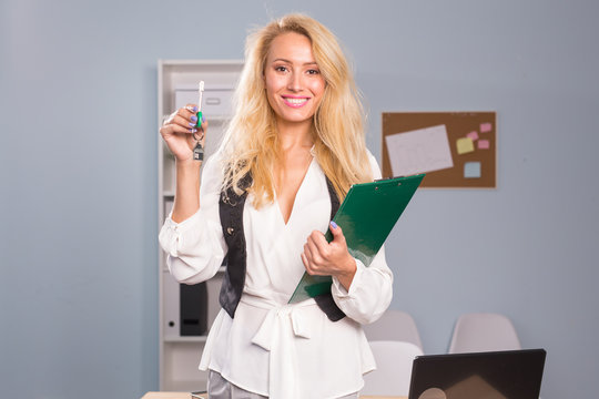 Business and people concept - a beautiful blonde realtor with files show keys from a new flat