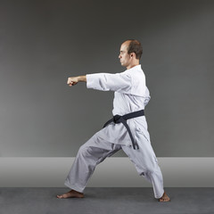 Adult man is training formal karate exercises on a gray background
