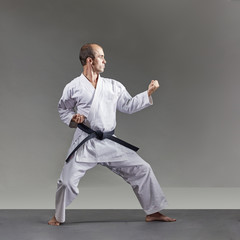A man in karategi trains formal karate exercises on a gray background