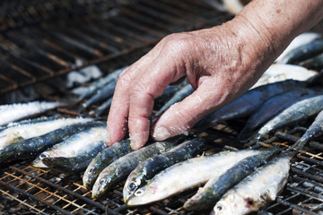 old woman salting some sardines in a grill