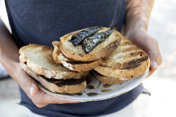 man with a plate of bread and sardines