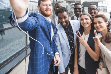 Self portrait of stylish successful, professional team, afro-american black man with stubble shooting selfie with hand on smart phone with friends, together standing in work place, station