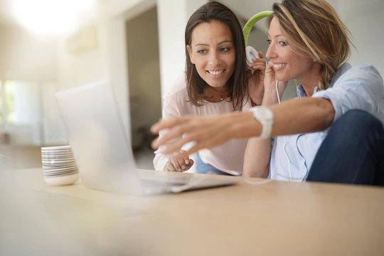 Girl friends listening to music on internet