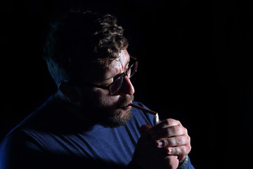 man brunette with a cigarette in the dark