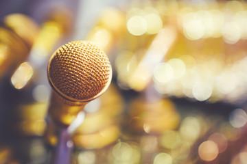 Golden microphone on blur beautiful bokeh background