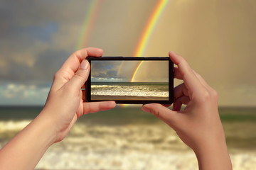 Female taking picture on mobile phone of double rainbow over ocean and tropical beach with umbrellas chairs and tables.